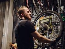 Przystojna rudzielec samiec w cajgu coverall, pracuje z rowerowym toczy wewnątrz remontowego sklep Pracownik usuwa bicykl Fotografia Royalty Free