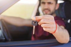 Przystojna samiec trzyma samochodu klucz sprzedaje jego samochód, travells w długiej podróży podczas gdy siedzi w samochodzie, Mę fotografia stock