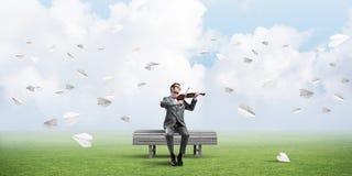 Przystojna skrzypaczka w parku na drewnianej ławki sztuce jego melodia fotografia royalty free