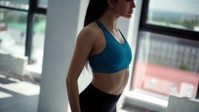 Przystojna sporty kobieta w sportswear robi rozciąganiu szyja w zwolnionym tempie zbiory