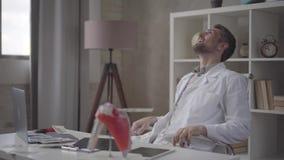 Przystojna szczęśliwa pomyślna, zadowolona brodata lekarka siedzi w krześle przy pracującym stołem w, rozprasza dolary zdjęcie wideo