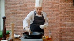 Przystojna szefa kuchni narządzania niecka z ciastem naleśnikowym i opowiadać kamera Zdjęcia Stock