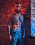 Przystojna tattoed bez koszuli samiec z ostrzyżeniem stoi przeciw ściana z cegieł w pokoju z loft elegancką brodą i, fotografia stock