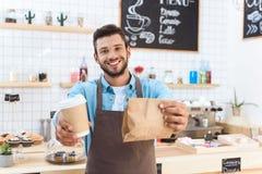 przystojna uśmiechnięta młoda barista mienia kawa iść w papierowej filiżance i brać oddalonego jedzenie Obrazy Royalty Free