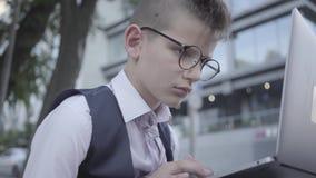 Przystojna ubierająca chłopiec siedzi na ulicznym działaniu na laptopie w górę w szkłach Poważny dzieciaka działanie lubi dorosłe zbiory