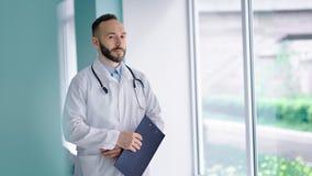 Przystojna ufna lekarka patrzeje okno i trzyma schowek w jego w białym żakiecie ręki zbiory