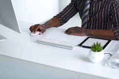 Przystojnego Afro Amerykański biznesmen w klasycznym kostiumu używa laptop i ono uśmiecha się podczas gdy pracujący w biurze Obrazy Royalty Free