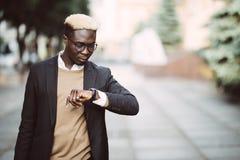 Przystojnego Afro Amerykański mężczyzna patrzeje zegarek jest ubranym kostium w nowożytnej miasto ulicie zdjęcie stock