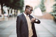 Przystojnego Afro Amerykański mężczyzna patrzeje zegarek jest ubranym kostium w nowożytnej miasto ulicie obraz royalty free