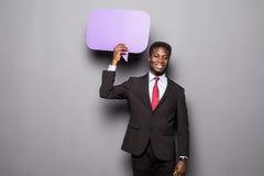 Przystojnego Afro Amerykański mężczyzna w klasycznym kostiumu trzyma bąbel stoi przeciw szarość mowy główkowanie i, Fotografia Royalty Free