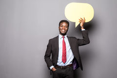 Przystojnego Afro Amerykański mężczyzna w klasycznym kostiumu trzyma bąbel stoi przeciw szarość mowy główkowanie i, Zdjęcie Stock
