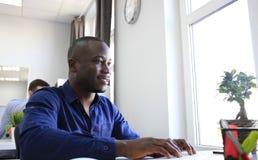 Przystojnego Afro Amerykański biznesmen pracuje w biurze Obrazy Royalty Free