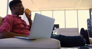 Przystojnego amerykanin afrykańskiego pochodzenia męski wykonawczy używa laptop w nowożytnym biurze 4k zbiory