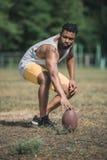 Przystojnego amerykanina afrykańskiego pochodzenia męski gracz futbolu z piłką na sądzie Obrazy Stock