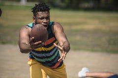 Przystojnego amerykanina afrykańskiego pochodzenia męski gracz futbolu z piłką na sądzie Fotografia Stock