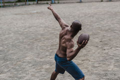 Przystojnego amerykanina afrykańskiego pochodzenia męski gracz futbolu z piłką na sądzie Zdjęcia Royalty Free