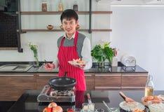 Przystojnego, Azjatyckiego młodego człowieka Uśmiechnięty szczęście, Trzymać smażącą kiełbasę na naczyniach fotografia stock