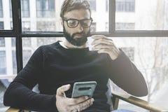 Przystojnego brodatego mężczyzna oka wering szkła pije kawę w domu i używa telefon komórkowego Przypadkowy relaksujący i spoczynk obrazy stock