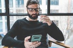 Przystojnego brodatego mężczyzna oka wering szkła pije kawę w domu i używa telefon komórkowego Przypadkowy relaksujący i spoczynk obrazy royalty free