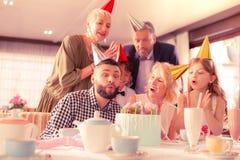 Przystojnego ciemnowłosego mężczyzny podmuchowe świeczki świętuje urodziny zdjęcie stock