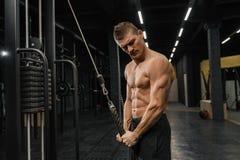 Przystojnego faceta stażowy triceps w gym pompuje w górę ciała bodybuilding obrazy royalty free