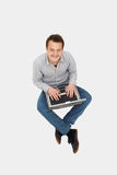 przystojnego laptopu przyglądający mężczyzna w górę potomstw zdjęcie stock