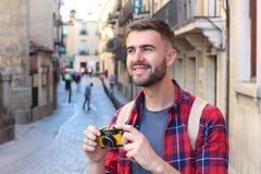 Przystojnego mężczyzna przyglądający oddalony mienie rocznik kamera podczas wycieczki Obraz Stock