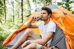 Przystojnego mężczyzna turystyczny obsiadanie i pić od kolby w lesie obrazy stock