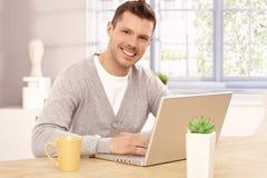 Przystojnego mężczyzna wyszukuje internet ono uśmiecha się w domu Zdjęcia Royalty Free