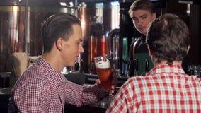 Przystojnego mężczyzny clinking szkła z jego przyjacielem, cieszy się pijący piwo z przyjacielem zbiory