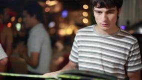 Przystojnego młodego człowieka czytelniczy menu w plenerowej kawiarni na zamazanym bokeh ulicy tle 1920x1080, hd zdjęcie wideo