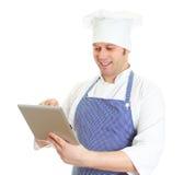 Przystojnego szefa kuchni pastylki kucbarski używa komputer osobisty. Obraz Stock