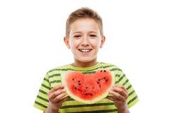 Przystojnego uśmiechniętego dziecko chłopiec mienia czerwonego arbuza owocowy plasterek fotografia royalty free