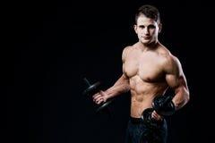 Przystojnej władzy mężczyzna sportowy szkolenie pompuje up mięśnie z dumbbells w gym Sprawności fizycznej mięśniowy ciało na czer Zdjęcia Stock