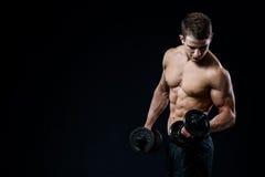 Przystojnej władzy mężczyzna sportowy szkolenie pompuje up mięśnie z dumbbells w gym Sprawności fizycznej mięśniowy ciało na czer Zdjęcie Stock