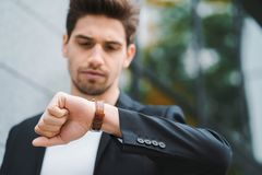 Przystojni biznesmena lub ucznia spojrzenia przy zegarkiem Młody człowiek w spiesznym dla pracy póżno Samiec model na budynku biu obraz royalty free