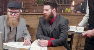 Przystojni brodaci freelancers dostaje kawowy i analizuje nowe inwestorskie możliwości zdjęcie wideo