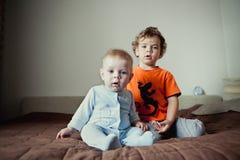 Przystojni chłopiec bracia siedzi obok each inny W domowym wnętrzu lifestyle obraz royalty free