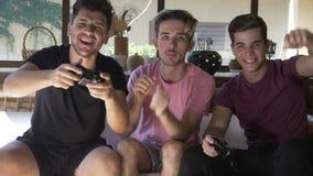 Przystojni faceci siedzi na leżance w holu bawić się wpólnie sieć gemowego używa joystick cieszy się drużynowego zwycięstwo - zdjęcie wideo