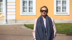Przystojni kobieta stojaki w tle okno piękny dom i uśmiechy, patrzeje kamerę zdjęcie wideo