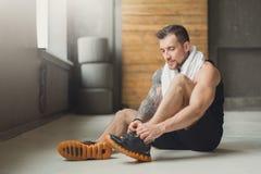Przystojni młody człowiek koronki buty przy gym po trenować fotografia stock