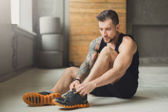 Przystojni młody człowiek koronki buty przy gym po trenować obrazy stock