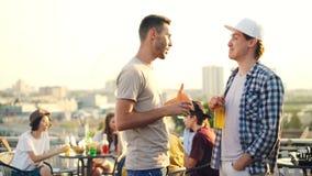 Przystojni młodych człowieków przyjaciele są opowiadający, gestykulujący i śmiający się mienie napoje podczas na otwartym powietr zbiory