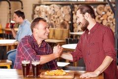Przystojni młodzi faceci spotykają w piwiarni Fotografia Stock