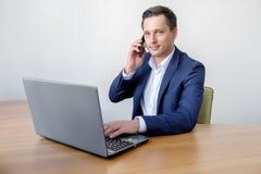 Przystojni potomstwa koncentrowali atrakcyjnego mężczyzna używa telefon komórkowego w biurze podczas gdy pracujący z laptopem obraz stock