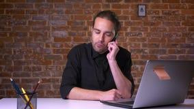 Przystojni potomstwa koncentruje mężczyzna mienia czekanie dla odpowiedzi i telefon podczas gdy patrzejący komputer podczas gdy s
