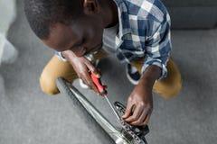przystojny afro mężczyzna naprawiania bicykl z śrubokrętem obraz stock
