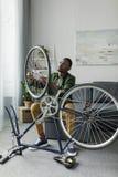 przystojny afro mężczyzna sprawdza rowerowego koło obraz royalty free