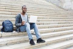 Przystojny afroamerykański mężczyzna z laptopem outdoors i kawą fotografia stock