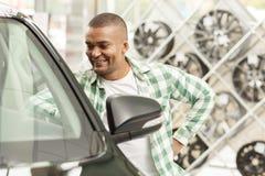 Przystojny Afrykański mężczyzna wybiera nowego samochód przy przedstawicielstwem handlowym zdjęcie royalty free